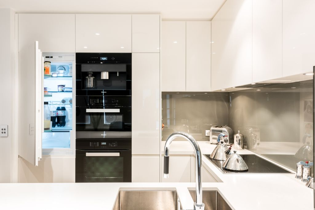 fully integrated modern kitchen, with silver taps and plain white design