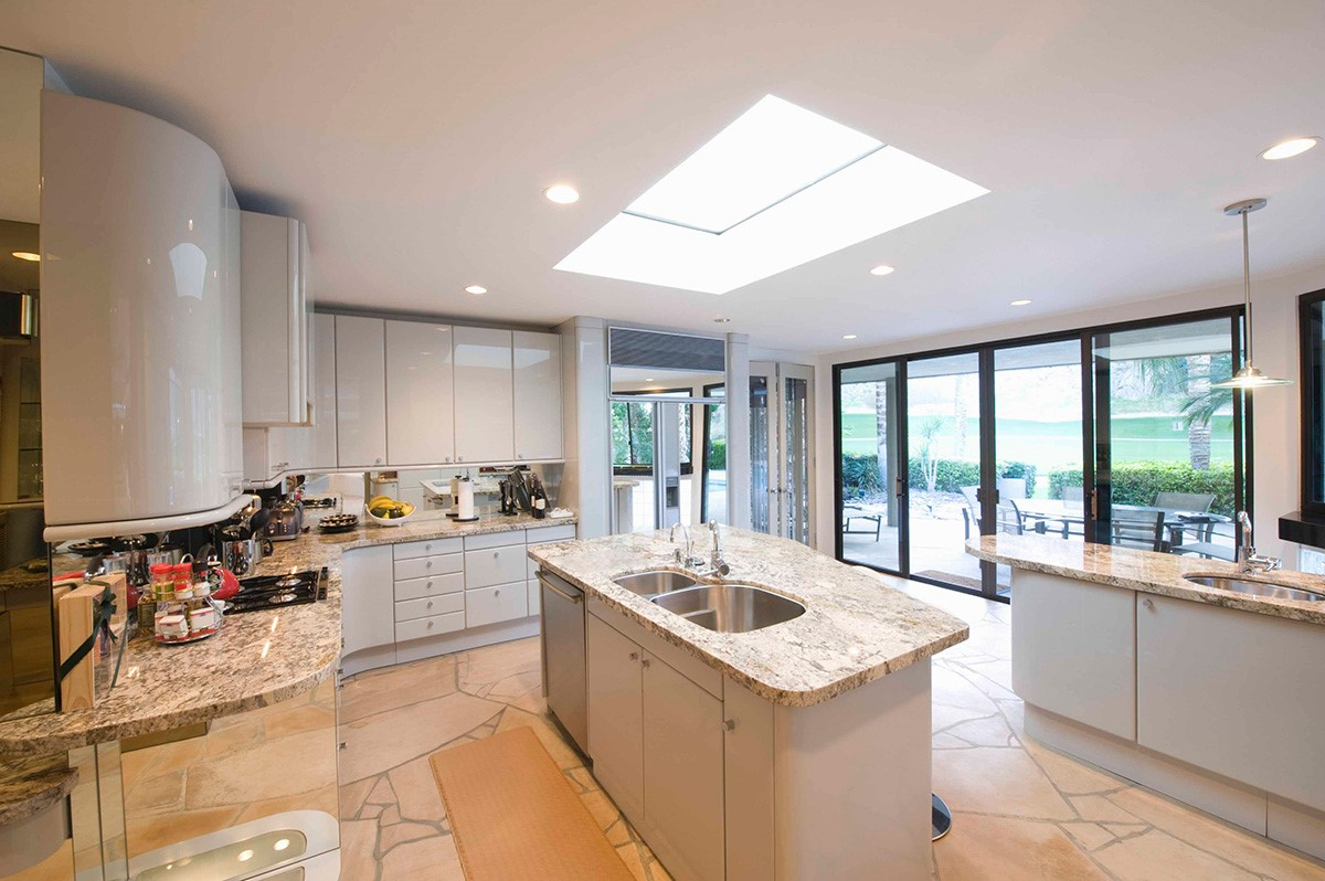 large bright kitchen with skylights and grey marble tops