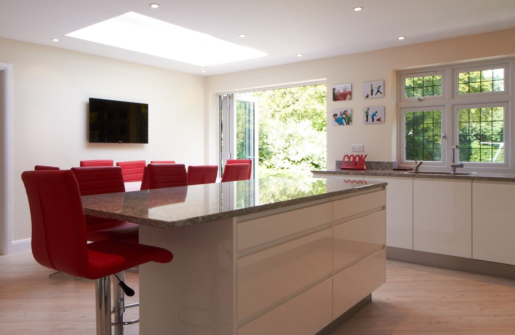 modern open plan kitchen with breakfast bar and red stools